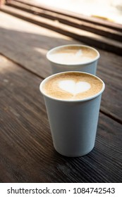 Two simple white paper cups of coffee take-away on wooden table.