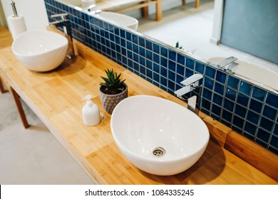 Two sinks in a bathroom with light brown wood base and beautiful blue mosaic wall, A soap dispenser and small plant in gray plant pot decorated with white and lighter gray patterns in the middle.