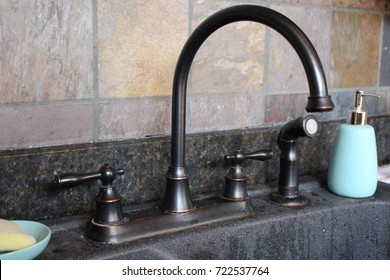 Two sinks with brass faucet and dark granite with tile back splash in kitchen