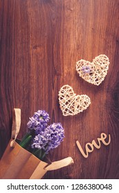 Two sisal hearts with love word and hiacinth flowers in a bag on rustic wooden background in flat lay with copy space. Birthday, Mother's, Valentines, Women's, Wedding Day concept.