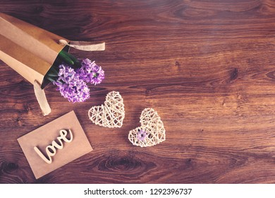 Two sisal hearts with love word and hyacinth flowers in an eco bag on rustic wooden background in flat lay with copy space. Birthday, Mother's, Valentines, Women's, Wedding Day concept.