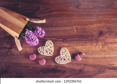 Two sisal hearts with macarons and hyacinth flowers in an eco bag on rustic wooden background in flat lay with copy space. Birthday, Mother's, Valentines, Women's, Wedding Day concept.