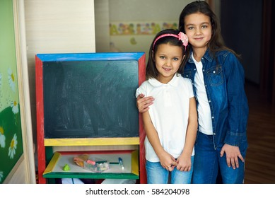 two sister girls standing at the net boards and hugging, looking into the camera. place for text.
