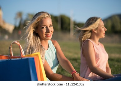 Two sister having a break after shopping in park, blonde pretty sibling looking at camera