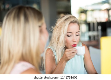 Two sister women in bar drinking coffee