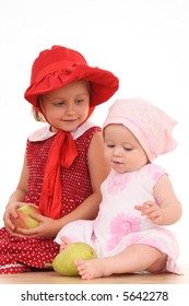 two sisters - 4 years old and 6 months with fruits isolated on white