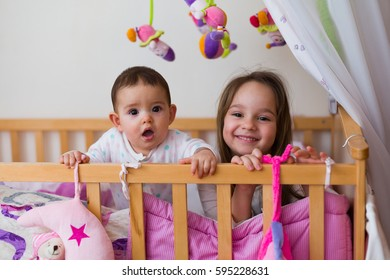 Two sisters in bed at night / in the morning spending playful time together.