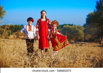 Two sisters and brother in folk Russian costumes at field.