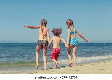 two sisters and brother playing on the beach at the day time