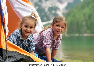 Two sisters camping at the lake, they enjoy playing in the tent, surrounded by nature. Concept of: sisterhood, travel, camping for children.