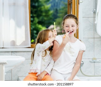 Two sisters cleaning the teeth together, morning, bathroom