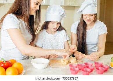 two sisters cooking with her mother in the kitchen. Infant Chef Concept.