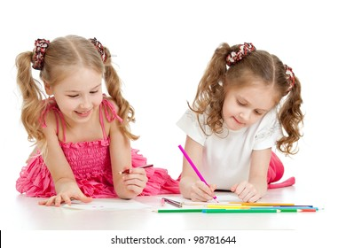 two sisters drawing with color pencils together over white