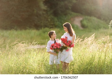 Two sisters dressed in white dresses have fun summertime together. Girls are holding flowers.