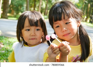 Two sisters are eating lollipops.