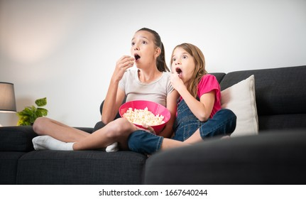 Two sisters eating popcorn in pink bowl and watching movie sitting on couch at home. Teenagers best friends with surprise face expression eating popcorn while watching a television film in their house