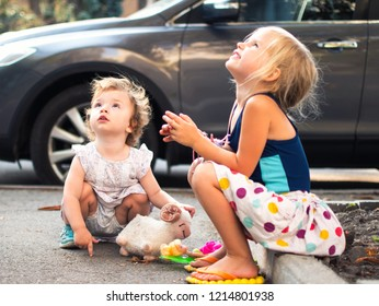 Two sisters girlfriends play on the sidewalk near the house