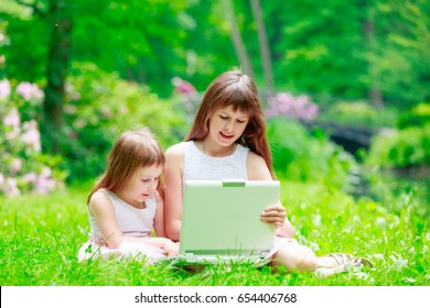 Two sisters have a fun with laptop on green grass in Park. Wroclaw, Poland