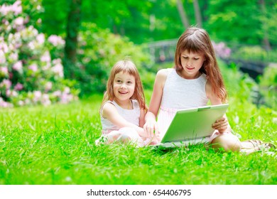 Two sisters have a fun with laptop in Park. Wroclaw, Poland