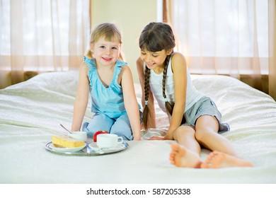 two sisters having breakfast in bed