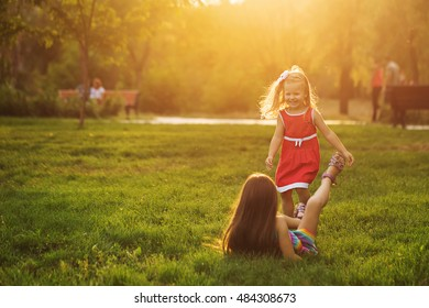 Two sisters having fun in the city park outdoors. The girl fell to the lawn. Freedom and carefree. Happy childhood.