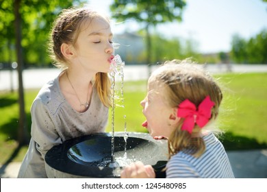 Two sisters having fun with drinking water fountain on warm and sunny summer day. Kids playing outdoors.