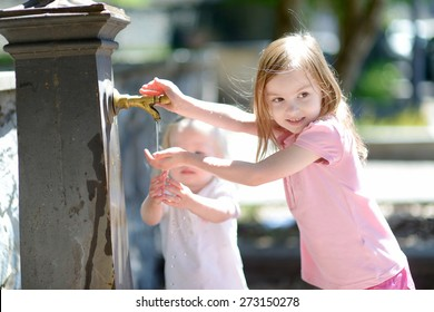 Two sisters having fun with drinking water fountain in Italy