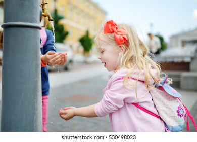 Two sisters having fun with drinking water fountain on warm and sunny summer day