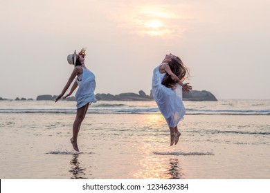 two sisters having fun at the sea at the sunset
