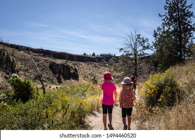 Two sisters hike with their dad at Smith Rock State Park in Central Oregon.
