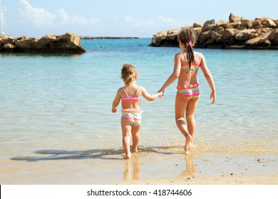 Two sisters holding hands and go swimming in the sea. Happy family vacation concept