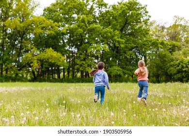 Two sisters hug one another outdoors, happy family