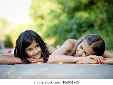 Two sisters laughing and playing with chalks on pavement in green sunny park
