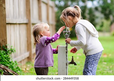 Two sisters- a little toddler girl and her older sister drinking water from the tap outside in the park in summer