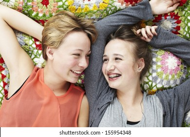 Two sisters lying on a blanket