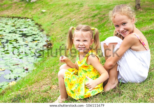 two sisters near a pond