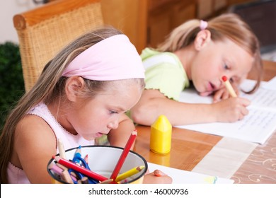Two sisters, one preschooler drawing, the older one doing homework for school