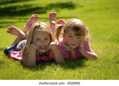 Two sisters in pink shirts resting their heads on their hands at the park