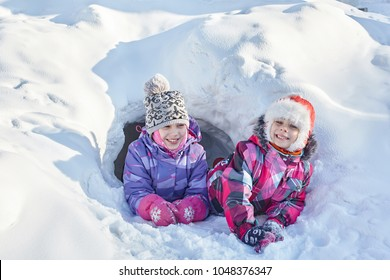 Two sisters play in the tunnel dug in a snowdrift