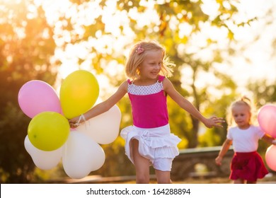 Two sisters playing in the park with balloons