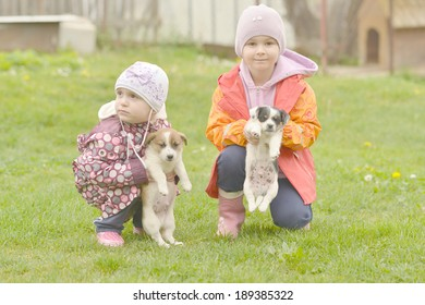 Two sisters playing with puppies