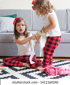 Two sisters quarrel, choosing clothes. Girls argue, fight, act up. Rivalry between children at home. The concept of the relationship between the sisters