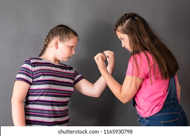 Two sisters quarreling and threatening fists to each other's