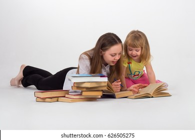 Two sisters reading together over white isolated background