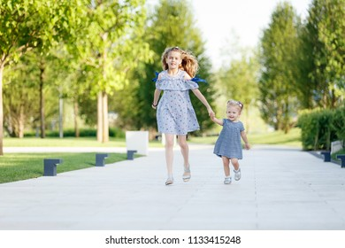 two sisters running down the road in the park