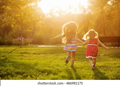 Two sisters running on the lawn in the city park outdoor. Freedom and carefree. Happy childhood. Man is unrecognizable.