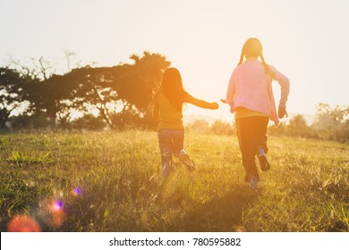 Two sisters running on the lawn in the city park outdoor. Freedom and carefree. Happy childhood. happy children running around outside playing catch-up concept