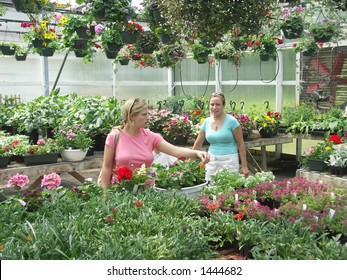 Two sisters shopping for plants and flowers at a greenhouse.