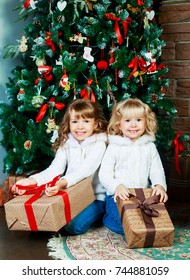 two sisters sitting on the floor at home with Christmas tree and presents
