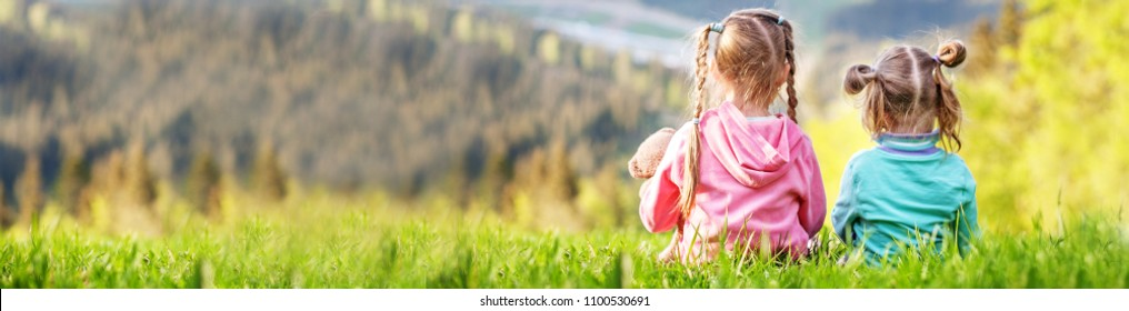 Two sisters sitting on the grass and look at the mountains. Banner for website. The concept of travel, lifestyle and family.